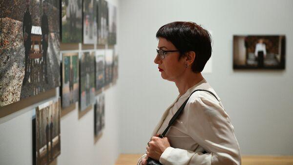Посетительница на открытии выставки победителей IV международного конкурса фотожурналистики имени Андрея Стенина в Москве - Sputnik Азербайджан