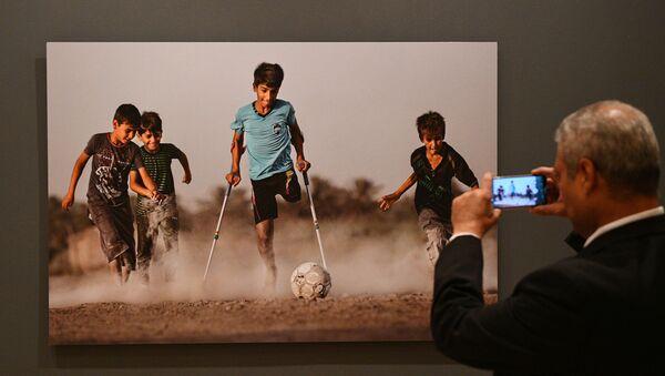 Посетитель на открытии выставки победителей IV международного конкурса фотожурналистики имени Андрея Стенина в Москве - Sputnik Азербайджан