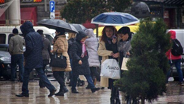 Люди идут по улице в дождь - Sputnik Азербайджан