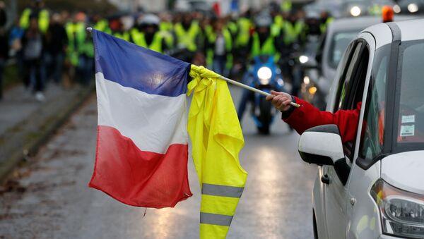 Протестующий держит французский флаг и желтый жилет в машине во время демонстрации движения желтые жилеты в Сомане, Франция, 8 декабря 2018 года - Sputnik Азербайджан