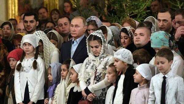 Rusiya prezidenti Vladimir Putin Sankt-Peterburqda kilsədə Milad ayini zamanı - Sputnik Azərbaycan