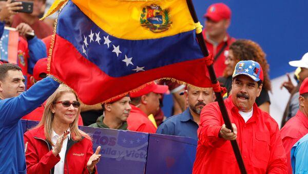 Президент Венесуэлы Николас Мадуро машет венесуэльским флагом со своей женой Силией Флорес во время митинга в поддержку правительства - Sputnik Azərbaycan