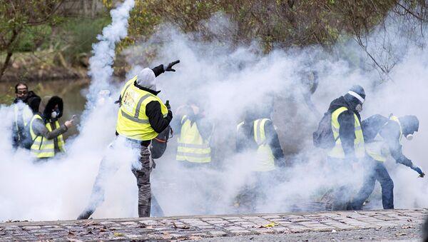 Демонстрант бросает дымовую гранату в ОМОН во время демонстрации протестующих Желтые жилеты (Gilets jaunes) в Нант, западная Франция - Sputnik Азербайджан