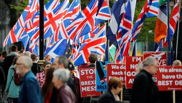 Активисты Брексита развевают флаги Союза, поскольку активисты антирекситского движения держат плакаты во время демонстрации возле Дома Парламента в Вестминстере, Лондон - Sputnik Азербайджан