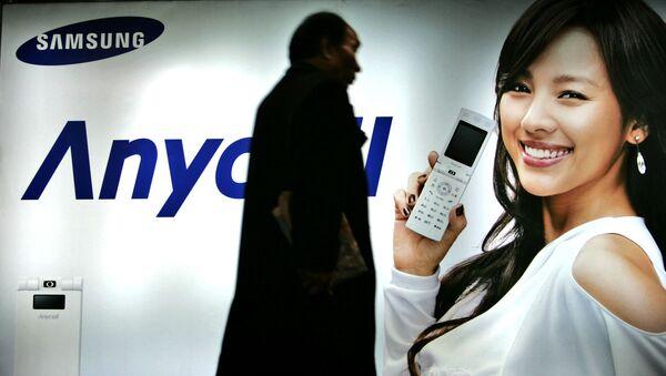Пешеход идет мимо рекламного щита Samsung Mobile в Сеуле, Южная Корея. 2007 год - Sputnik Азербайджан