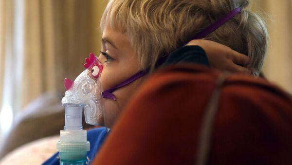 Мальчик сидит и смотрит мультфильм во время лечения астмы - Sputnik Азербайджан