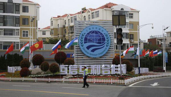 Полицейский стоит возле знака саммита Шанхайской организации сотрудничества (ШОС) в Циндао, провинция Шаньдун на востоке Китая - Sputnik Азербайджан