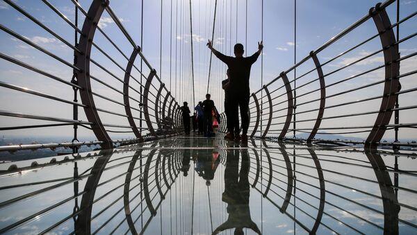 Люди фотографируются на 518-метровом мосте со стеклянным дном в Парке приключений Хуаси - Sputnik Азербайджан