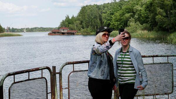 Туристы делают селфи в речном порту заброшенного города Припять. Вокруг — буйная растительность - Sputnik Азербайджан