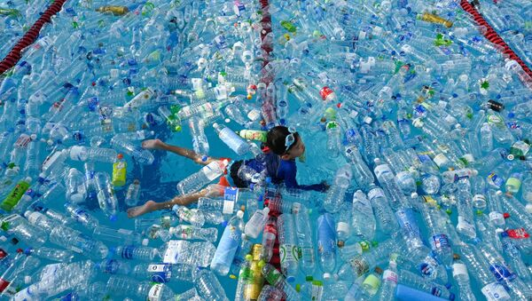 Ребенок плавает в бассейне, наполненном пластиковыми бутылками, во время информационной кампании, посвященной Всемирному дню океанов в Бангкоке, Таиланд - Sputnik Азербайджан