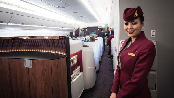 Стюардесса Qatar Airways улыбается пассажирам - Sputnik Азербайджан