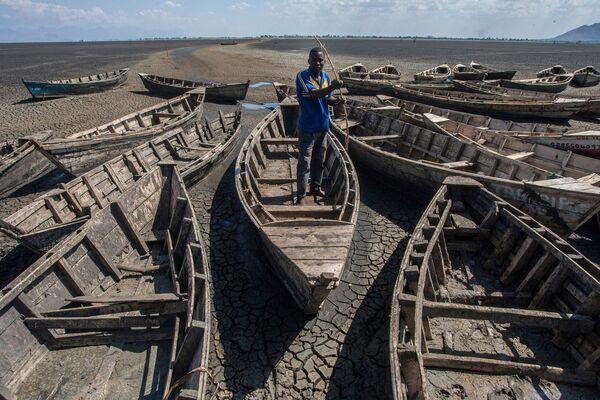Молодой рыбак среди лодок у высохшего в октябре 2018 года озера Чилва в Малави - Sputnik Азербайджан