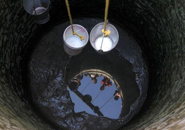 Индийские жители деревни Падал в округе Самба пытаются зачерпнуть воду в ведра - Sputnik Азербайджан