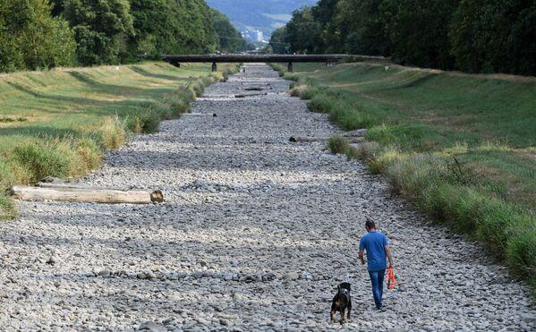 Человек гуляет со своей собакой по пересохшему руслу реки Драйзам - Sputnik Азербайджан