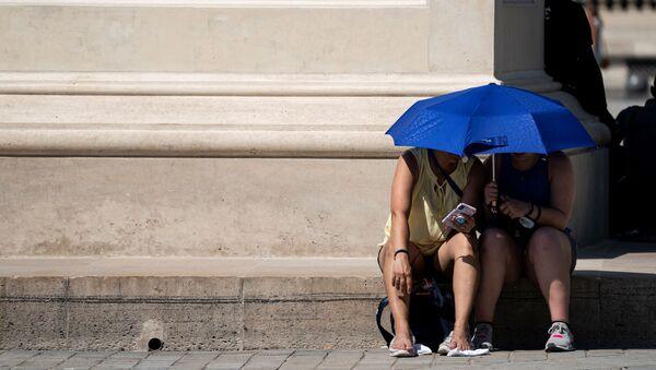 Девушки укрываются от солнца под зонтом, фото из архива - Sputnik Азербайджан
