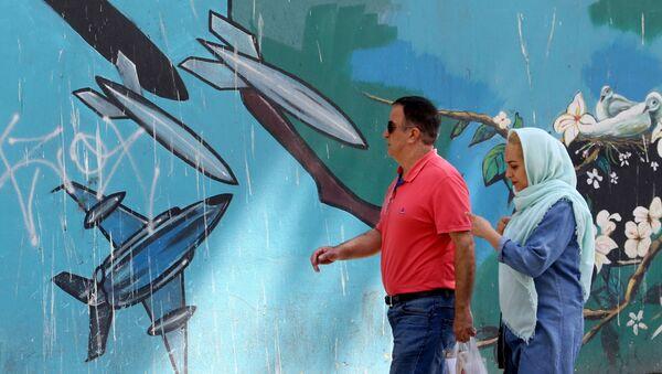 Люди проходят мимо настенной росписи вдоль стены бывшего посольства США в иранской столице Тегеране - Sputnik Азербайджан