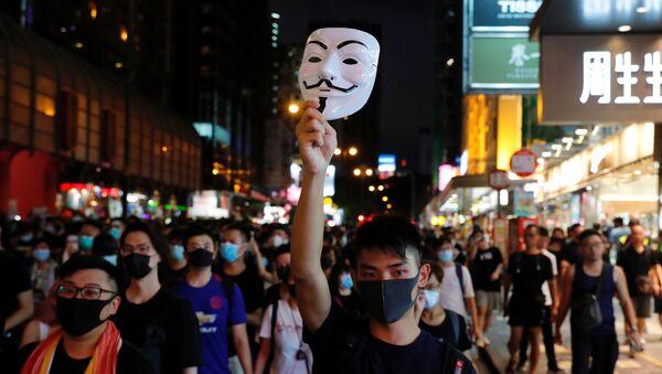Протестующий против выдачи законопроекта поднимает маску Гая Фокса, когда он марширует в туристическом районе Гонконга Натан-роуд около Монгкока - Sputnik Азербайджан