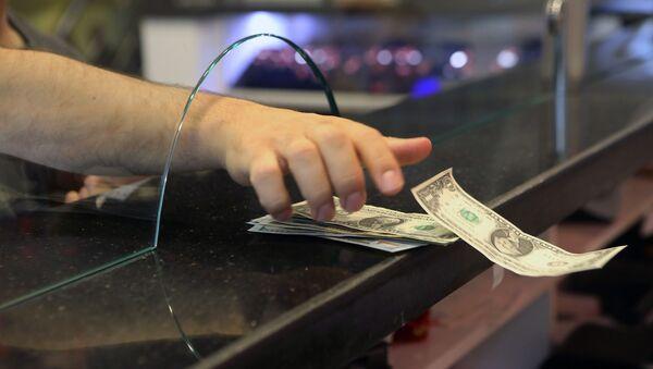 Клиент забирает банкноты в долларах США в пункте обмена валют, фото из архива - Sputnik Азербайджан