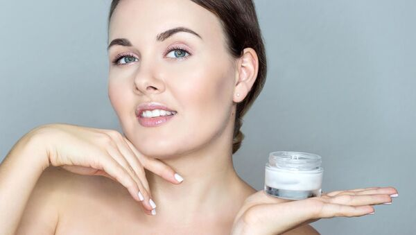 Девушка с легким макияжем держит крем для лица и улыбается - Sputnik Azərbaycan