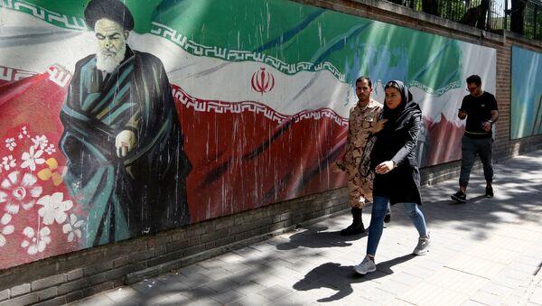 Люди проходят мимо фрески с изображением основателя исламской республики аятоллы Рухоллы Хомейни и государственного флага вдоль стены бывшего посольства США в иранской столице Тегеране 22 июня 2019 года - Sputnik Азербайджан