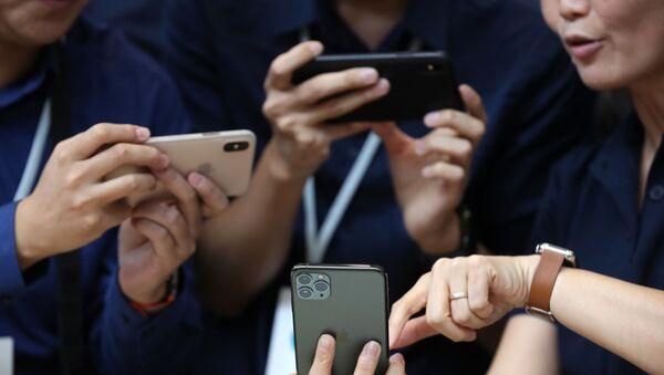 Посетители рассматривают новые Apple iPhone 11 Pro в Калифорнии  - Sputnik Азербайджан