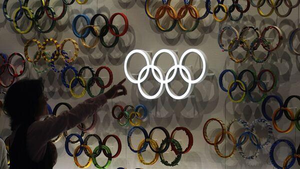 Посетитель показывает на недавно открывшийся Олимпийский музей Японии перед Олимпиадой в Токиo - Sputnik Азербайджан