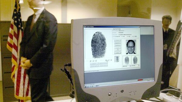 Сотрудник посольства США проходит мимо монитора, отображающего биометрические данные во время демонстрации новой процедуры, сканирования отпечатков пальцев в посольстве США в Москве - Sputnik Азербайджан