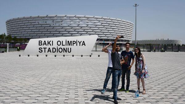 Прохожие фотографируются у Национального олимпийского стадиона в Баку - Sputnik Азербайджан