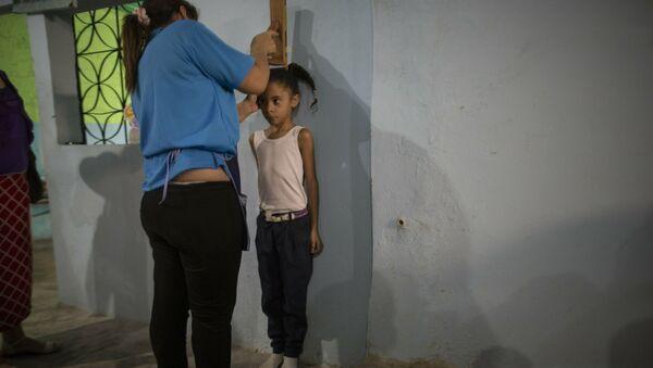 Социальный работник измеряет рост девочки, фото из архива - Sputnik Азербайджан