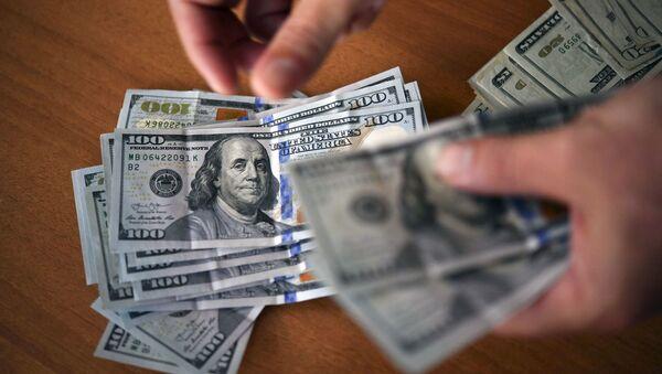 Человек считает доллары, фото из архива - Sputnik Азербайджан