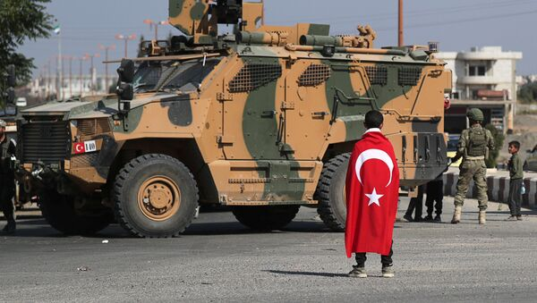 Мальчик укутанный в турецкий флаг стоит перед турецким военным транспортным средством в городе Тал Абьяд в Сирии - Sputnik Азербайджан