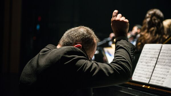 Человек, сидящий перед сборником песен - Sputnik Azərbaycan