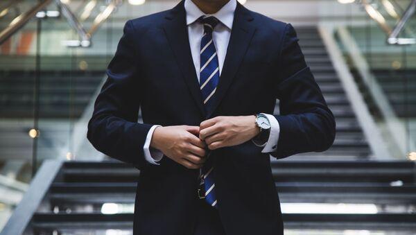 Мужчина в деловом костюме синего цвета и полосатом галстуке застегивает пиджак - Sputnik Азербайджан