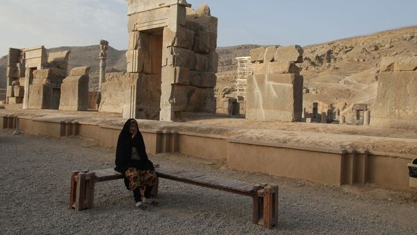 Иранская женщина на скамейке среди руин древнего имперского города Персеполис - Sputnik Азербайджан