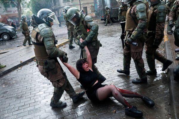 Раненая участница митинга против правительства Чили во время задержания - Sputnik Азербайджан