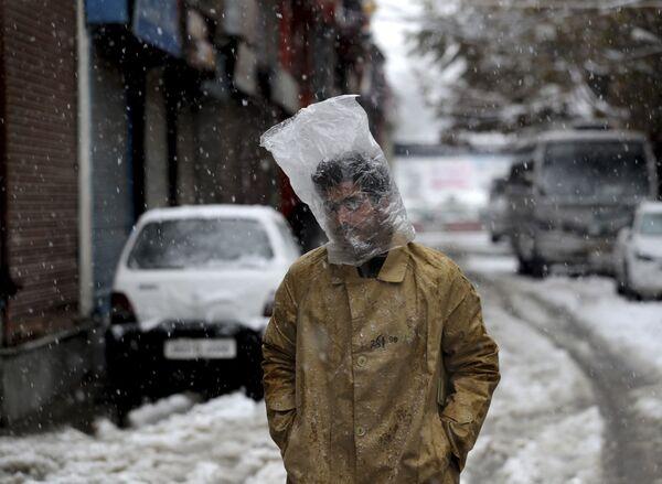 Мужчина прикрывает голову полиэтиленовым пакетом во время снегопада в Сринагаре, Кашмир - Sputnik Азербайджан