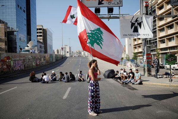 Женщина с флагом Ливана во время антиправительственных протестов в Бейруте - Sputnik Азербайджан