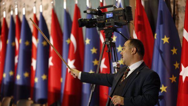 Чиновник направляет помощников, чтобы скорректировать флаги Турции и Европы перед открытием заседания высокого уровня между ЕС и Турцией в Стамбуле - Sputnik Азербайджан