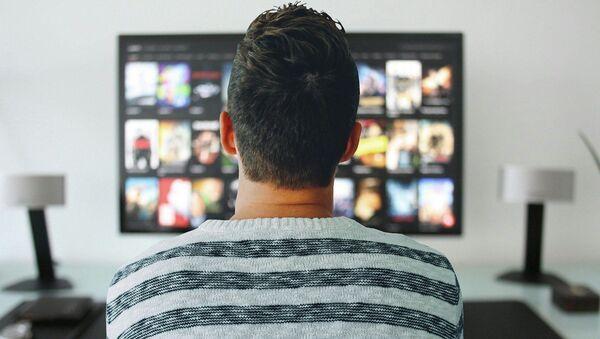 Мужчина смотрит телевизор, фото из архива - Sputnik Азербайджан