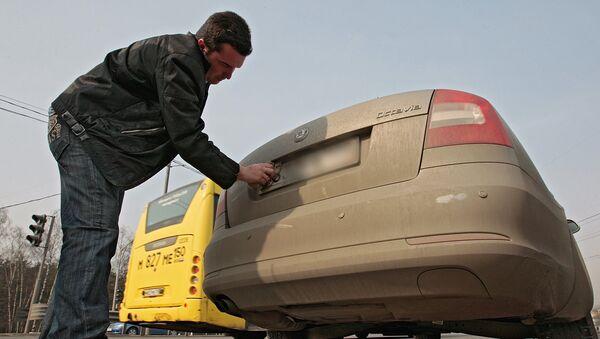 Автовладелец моет номерной знак своего автомобиля - Sputnik Азербайджан