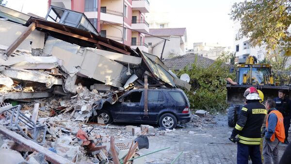 Пожарные стоят рядом с разрушенным зданием после землетрясения в Албании - Sputnik Азербайджан