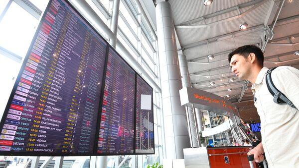 Пассажир изучает информационное табло с расписанием авиарейсов - Sputnik Азербайджан
