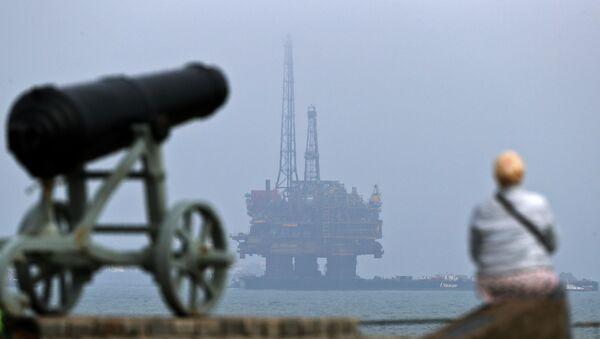 Мужчина смотрит на нефтяную платформу Brent Delta у побережья Хартлпула на северо-востоке Англии - Sputnik Азербайджан