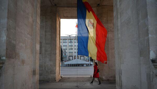 Женщина идет под Триумфальной аркой рядом с молдавским флагом в Кишиневе - Sputnik Азербайджан