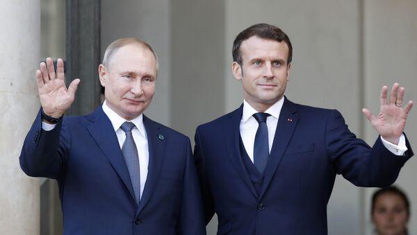 Президент Эммануил Макрон (справа) и президент России Владимир Путин машут в Елисейском дворце в понедельник, 9 декабря 2019 года в Париже - Sputnik Азербайджан