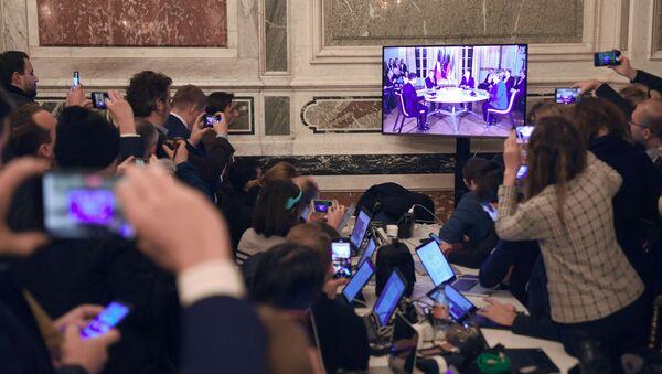 Журналисты смотрят трансляцию встречи глав государств-участников Нормандского формата в Елисейском дворце - Sputnik Азербайджан