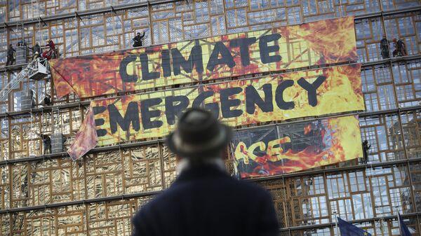 Мужчина смотрит на активистов по борьбе  с изменением климата, фото из архива - Sputnik Азербайджан