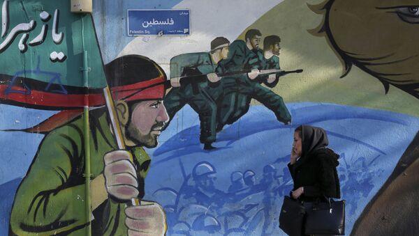 Иранская женщина проходит мимо фрески с изображением иранских вооенных в Тегеране - Sputnik Азербайджан