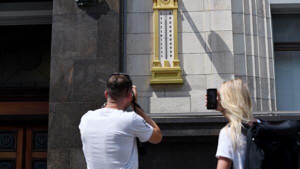 Молодые люди фотографируют термометр - Sputnik Азербайджан