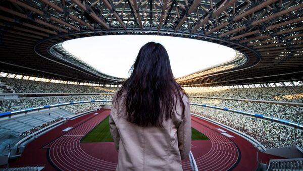 Журналист смотрит на Национальный стадион, место проведения предстоящих Олимпийских игр в Токио 2020 - Sputnik Азербайджан